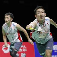 Keigo Sonoda (left) hits a return as doubles partner Takeshi Kamura looks on in the World Badminton Championships on Friday in Nanjing, China. The duo advanced to the semifinals by beating Indonesia's Marcus Gideon and Kevin Sukamuljo 21-19, 21-18. | KYODO