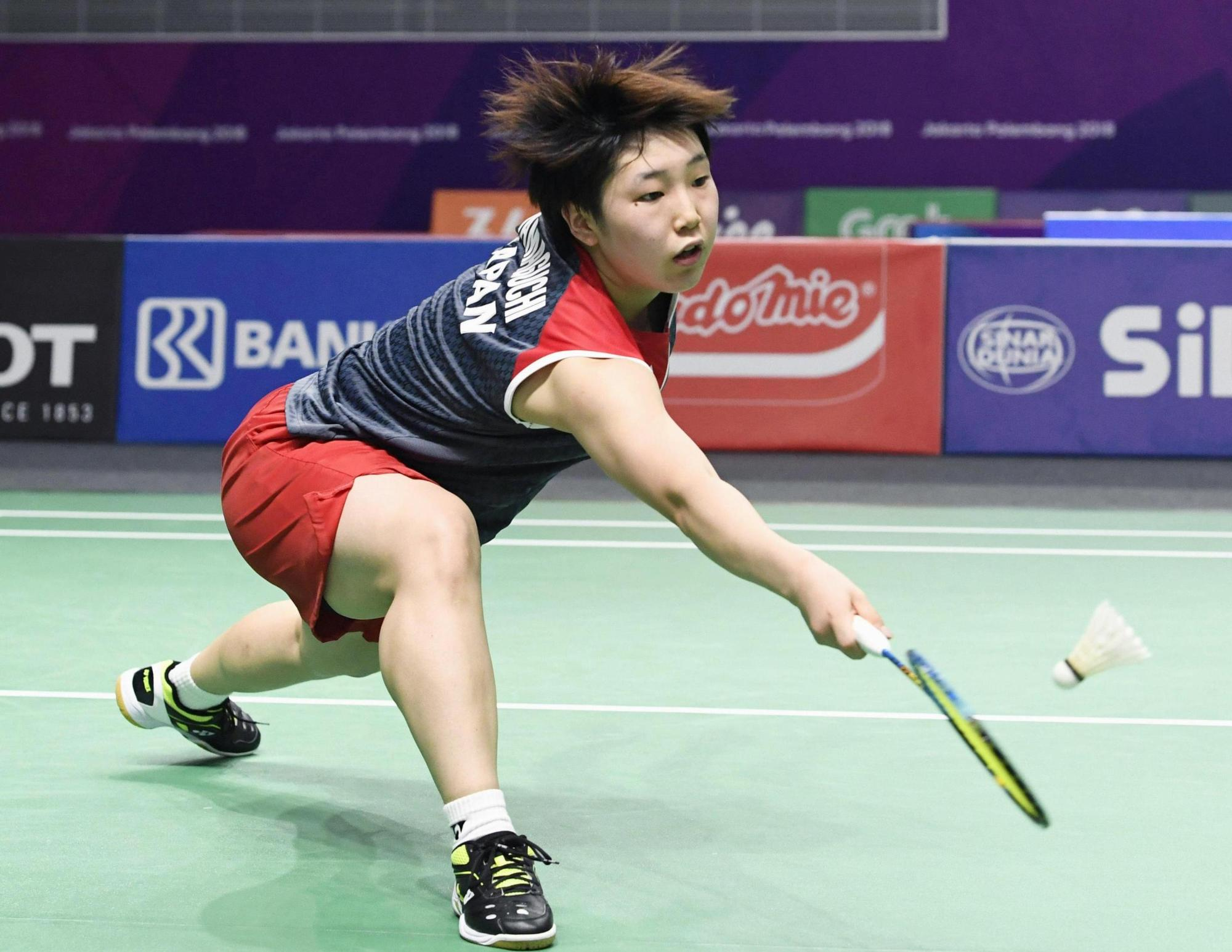 Akane Yamaguchi hits the shuttlecock in the first game of her match against Indonesia's Gregoria Mariska Tunjung in the women's team semifinal on Tuesday in Jakarta. Yamaguchi lost 21-16, 9-21, 21-18, but Japan advanced to the final. | KYODO