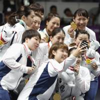 The Japanese team takes a selfie after winning the women's badminton team gold medal at the Asian Games on Wednesday in Jakarta. | REUTERS