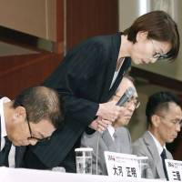Japan Basketball Association chief Yuko Mitsuya bows in apology before announcing the year-long ban of four players involved in a sex scandal at the Asian Games. | KYODO