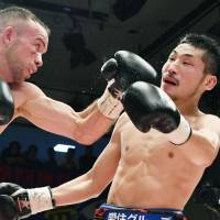 TJ 'The Power' Doheny (left) punches Ryosuke Iwasa in the 11th round of their IBF super bantamweight title fight on Thursday at Korakuen Hall. Doheny beat the champion by unanimous decision. | KYODO