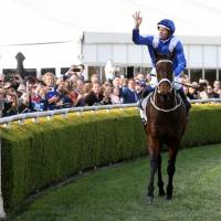 Jockey Hugh Bowman gestures after he rode Winx to victory in the Winx Stakes at Royal Randwick in Sydney on Saturday.