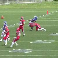 A Nihon University defender (top right) makes an illegal tackle on the Kwansei Gakuin quarterback  during an exhibition game on May 6 in Tokyo. | KYODO