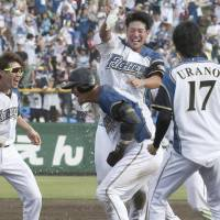 The Fighters throw water on Sho Nakata (center) after his game-winning hit against the Marines on Wednesday in Obihiro, Hokkaido. | KYODO