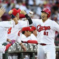 Carp slugger Seiya Suzuki (right) is congratulated by teammates after bashing a solo home run in the third inning against the Dragons on Tuesday at Nagoya Dome. Hiroshima topped Chunichi 6-2. | KYODO