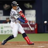 The Buffaloes' Ryoichi Adachi delivers a three-run triple in the eighth inning against the Marines at Kyocera Dome on Saturday. Orix rallied to beat Chiba Lotte 6-3. | KYODO