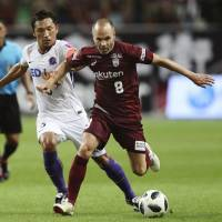 Vissel's Andres Iniesta (right) controls the ball while being defended by Sanfrecce's Toshihiro Aoyama during their match on Wednesday in Kobe. | KYODO