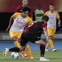 Red Bull Salzburg's Takumi Minamino takes on Shkendija's Armend Alimi during their Champions League qualifier on Tuesday in Skopje. | AP