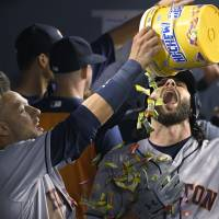 The Astros' Yuli Gurriel (left) pours Hi-Chew on Jake Marisnick, who had returned to the dugout after hitting a two-run homer against the Dodgers on Saturday in Los Angeles. | AP