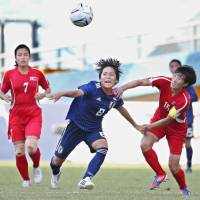 Japan's Mana Iwabuchi (center) looks to control the ball against North Korea in the Asian Games women's soccer tournament quarterfinals on Saturday in Palembang, Indonesia. Iwabuchi scored the first goal of the match, which Japan won 2-1.   KYODO