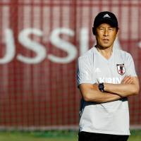 Former national team manager Akira Nishino watches his players during a training session at Japan's base in Kazan, Russia, during the World Cup in June. | KYODO