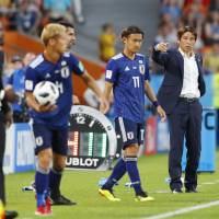 Akira Nishino instructs his players during Japan's 2-2 draw with Senegal at the World Cup in June. | KYODO