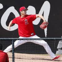 The Angels' Shohei Ohtani pitches during a bullpen session on Saturday in Anaheim, California. | KYODO