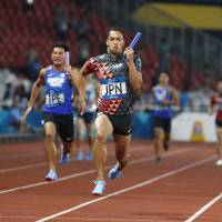 Japan's Asuka Cambridge crosses the finish line first in the men's 4x100-meter relay at the Asian Games on Thursday in Jakarta. Japan won the event for the first time in 20 years at the Asian Games. | AP