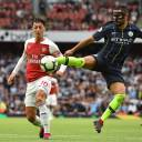 Manchester City's Ilkay Gundogan (right) kicks the ball in front of Arsenal's Mesut Ozil during their match on Sunday in London.