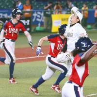 Japan pitcher Yukiko Ueno (center) reacts as the U.S. players celebrate their victory in the Women's World Softball Championship final on Sunday in Chiba. | KYODO