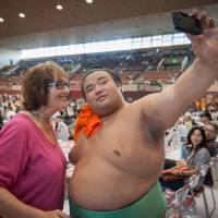 Takakeisho takes a picture with a fan at a regional tour event in Sendai in this August 2016 file photo. | JOHN GUNNING