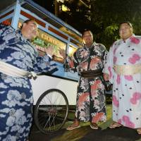 Sumo wrestlers stand beside a street food cart in Jakarta during a tour to the Indonesian capital in 2013. | KYODO