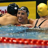Canada's Kylie Masse (center) celebrates after winning the women's 100-meter backstroke final on Friday.