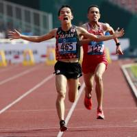 Hiroto Inoue crosses the finish line ahead of Bahrain's Elhassan Elabbassi to win the men's marathon at the Asian Games on Saturday. | AP