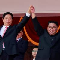 North Korean leader Kim Jong Un and China's Li Zhanshu, chairman of the Standing Committee of the National People's Congress (NPC), wave to people while attending a military parade marking the 70th anniversary of North Korea's foundation in Pyongyang on Sunday. | REUTERS