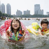 Children swim in the ocean at Odaiba Beach in July 2014. | KYODO