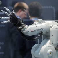 A Mitsubishi Melfa robotic arm, manufactured by Mitsubishi Electric Corp., is displayed at the Robert Bosch GmbH Internet of Things conference in Berlin in February. | BLOOMBERG
