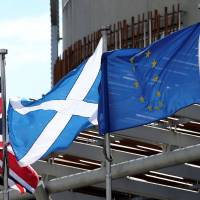 The Union Jack, Scottish Soltaire and European Union flags (from left) fly outside of the Scottish Parliament building in Edinburgh in 2016. | SCOTT HEPPELL / VIA REUTERS