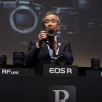 Masaya Maeda, president and chief operating officer of Canon Inc., holds a Canon EOS R, the company's new mirrorless digital camera, at an unveiling event in Tokyo Wednesday. | BLOOMBERG