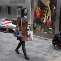 A shopper wearing a mask against pollution walks past a U.S, apparel store in Beijing in March. China faces bigger economic challenges than its trade war with the U.S. Even before tit-for-tat tariffs, growth in the world's No. 2 economy was already forecast to cool from 6.8 percent last year to a still-robust 6.5 percent this year. Growth in retail sales, a bigger part of the Chinese economy than exports, was weaker than expect in July and close to a 14-year low. Factory output and other sectors also decelerated. | NG HAN GUAN / VIA AP