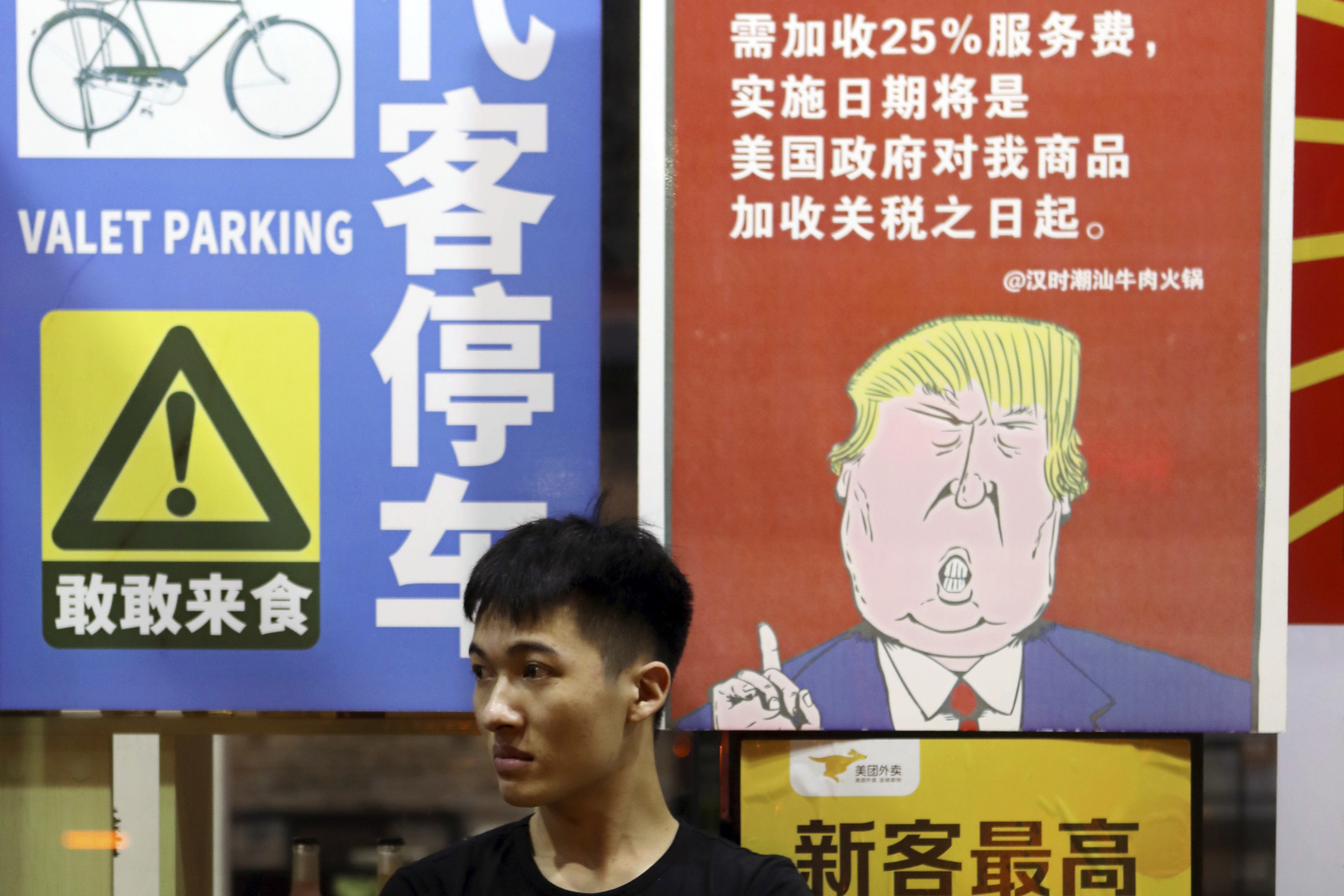 A man sits in front of a billboard stating that American customers will be charged 25 percent extra due to ongoing China-U.S. trade tensions at a restaurant in Guangzhou in southern China's Guangdong Province on Aug. 13. | CHINATOPIX / VIA AP