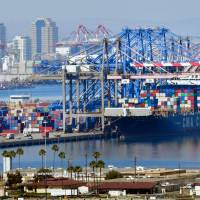 Shipping containers are loaded onto vessels at the Port of Long Beach in Long Beach, California, in July. | AFP-JIJI