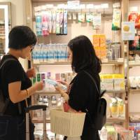 Shoppers check items at an @cosme store run by istyle Inc., the operator of Japan's popular beauty and cosmetic products portal site @cosme, at the Star House commercial complex in Hong Kong's bustling Tsim Sha Tsui shopping district on Sept. 3. | NNA/KYODO