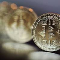 Bitcoin tokens are displayed. The Financial Services Agency has tightened its registration screening process for cryptocurrency exchanges to determine whether risk management is being properly conducted. | BLOOMBERG