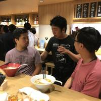 Fukuoka Mayor Soichiro Takashima (second from right) talks to participants at a ramen shop and bar in Tokyo's Minato Ward during an event organized by the city of Fukuoka on Aug. 21 to encourage engineers to move to the city. | KAZUAKI NAGATA