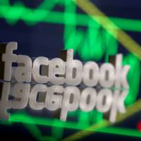 A 3D-printed Facebook logo is seen in front of displayed stock graph in this illustration photo in March.   REUTERS
