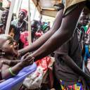 A mother weighs her malnourished child in a nutrition center run by the International Rescue Committee (IRC) in Panthau, Northern Bahr al Ghazal, South Sudan, in 2017.