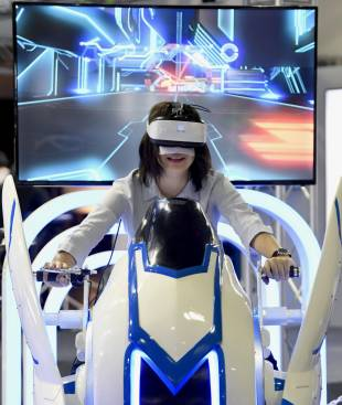A visitor tries out a virtual reality motorcycle at the Tokyo Game Show, which kicked off Thursday.