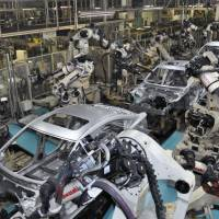 Robot arms assemble car bodies on a production line at a Mazda Motor Corp. plant in Hofu, Yamaguchi Prefecture. Japan's gross domestic product for the April-June quarter has been revised upward to an annual rate of 3.0 percent. | KYODO