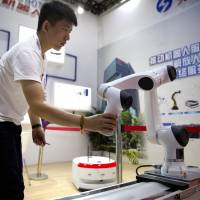 A visitor looks at a robotic manufacturing arm from Chinese robot maker Han's Robots at the World Robot Conference in Beijing in August. | AP