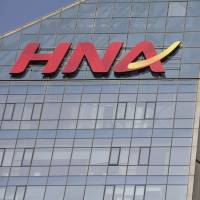 Signage for HNA Group Co. is displayed atop company premises in Beijing. | BLOOMBERG
