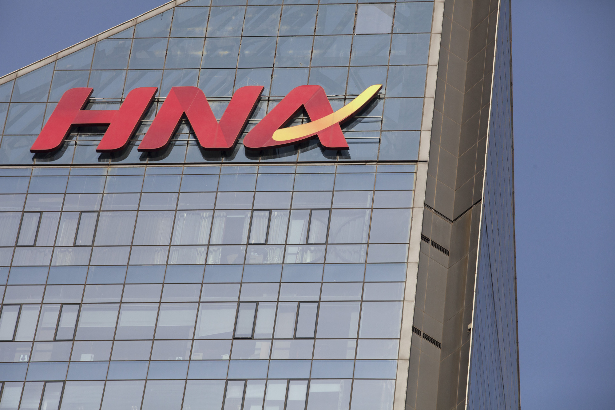 Signage for HNA Group Co. is displayed atop company premises in Beijing.   BLOOMBERG
