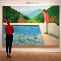 A woman looks at David Hockney's 'Portrait of an Artist (Pool with Two Figures)' during a press preview on Thursday at Christie's New York. — The painting is to be auctioned during Christie's November 2018 Evening Sale of Post-War and Contemporary Art. | TIMOTHY A. CLARY / VIA AFP-JIJI