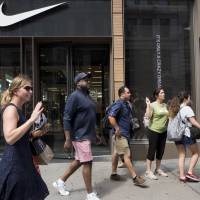 People pass a Nike store in New York Tuesday. An endorsement deal between Nike and Colin Kaepernick is prompting a flood of debate online as sports fans react to the apparel giant backing an athlete known mainly for starting a wave of protests among NFL players of police brutality, racial inequality and other social issues. | AP