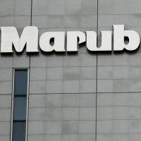 The logo of Marubeni Corp. is seen at the company headquarters in Tokyo on May 10, 2016. Marubeni said it will halve its net coal power-generating capacity by 2030. | REUTERS