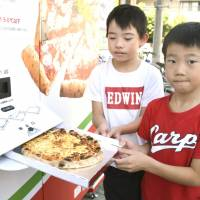 Children pull out freshly made pizza from a vending machine in Hiroshima on Sept. 2. | KYODO
