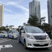 Self-driving cars are parked in front of the headquarters of NTT Data Corp. in Tokyo's Toyosu district on Thursday. | KAZUAKI NAGATA
