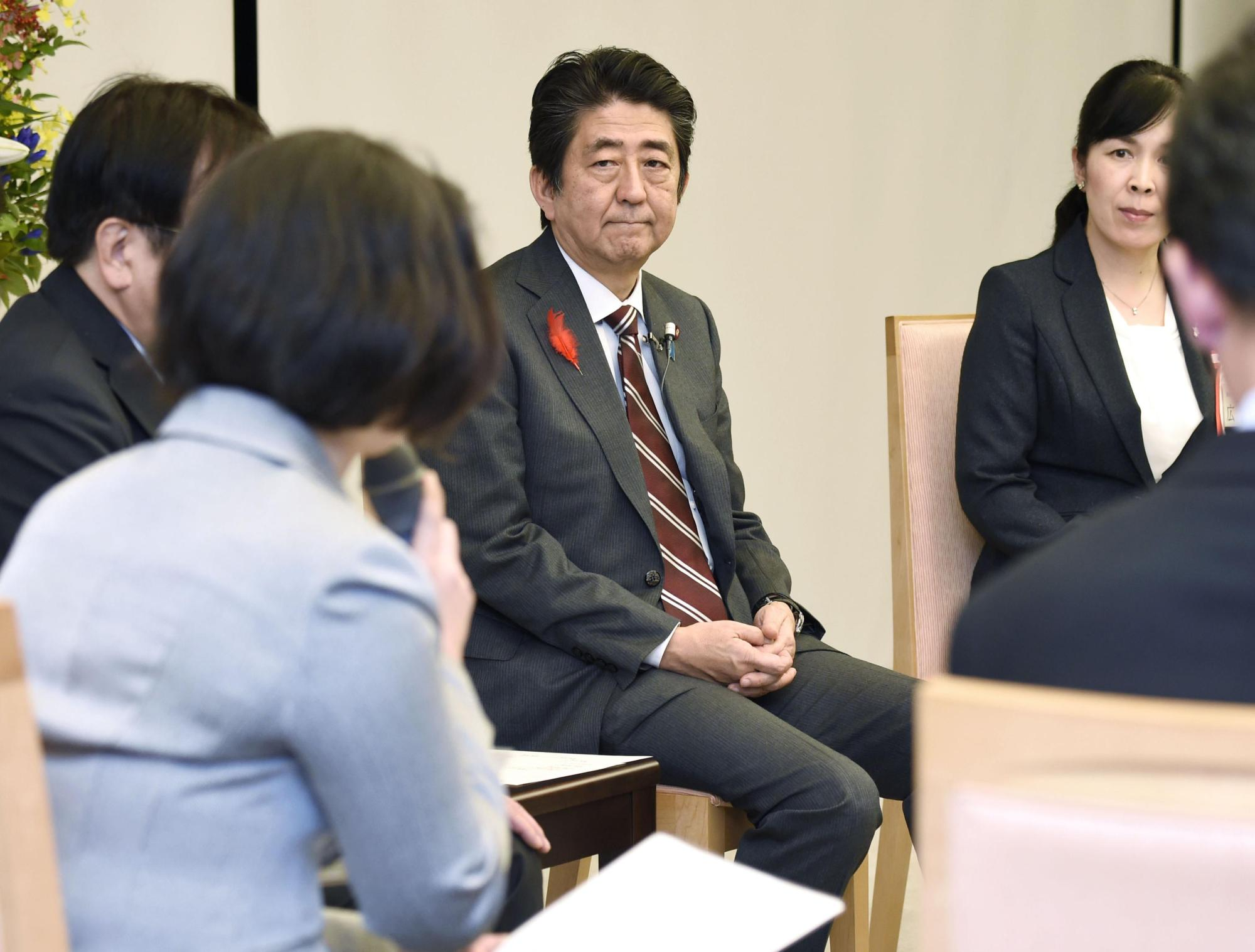 Prime Minister Shinzo Abe holds a meeting with people who have experiences in changing jobs or doing side jobs at the Prime Minister's Office in October 2016. | KYODO