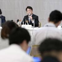 Michio Arikuni, newly appointed president of Suruga Bank (center), speaks at a news conference in Numazu, Shizuoka Prefecture, on Friday. | KYODO
