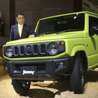 Suzuki Motor Corp. President Toshihiro Suzuki stands beside a new model of its Jimny four-wheel-drive minivehicle series in Tokyo's Shibuya Ward on July 5. The carmaker plans to withdraw from the Chinese market as consumers there shift their preferences toward larger automobiles. | KYODO